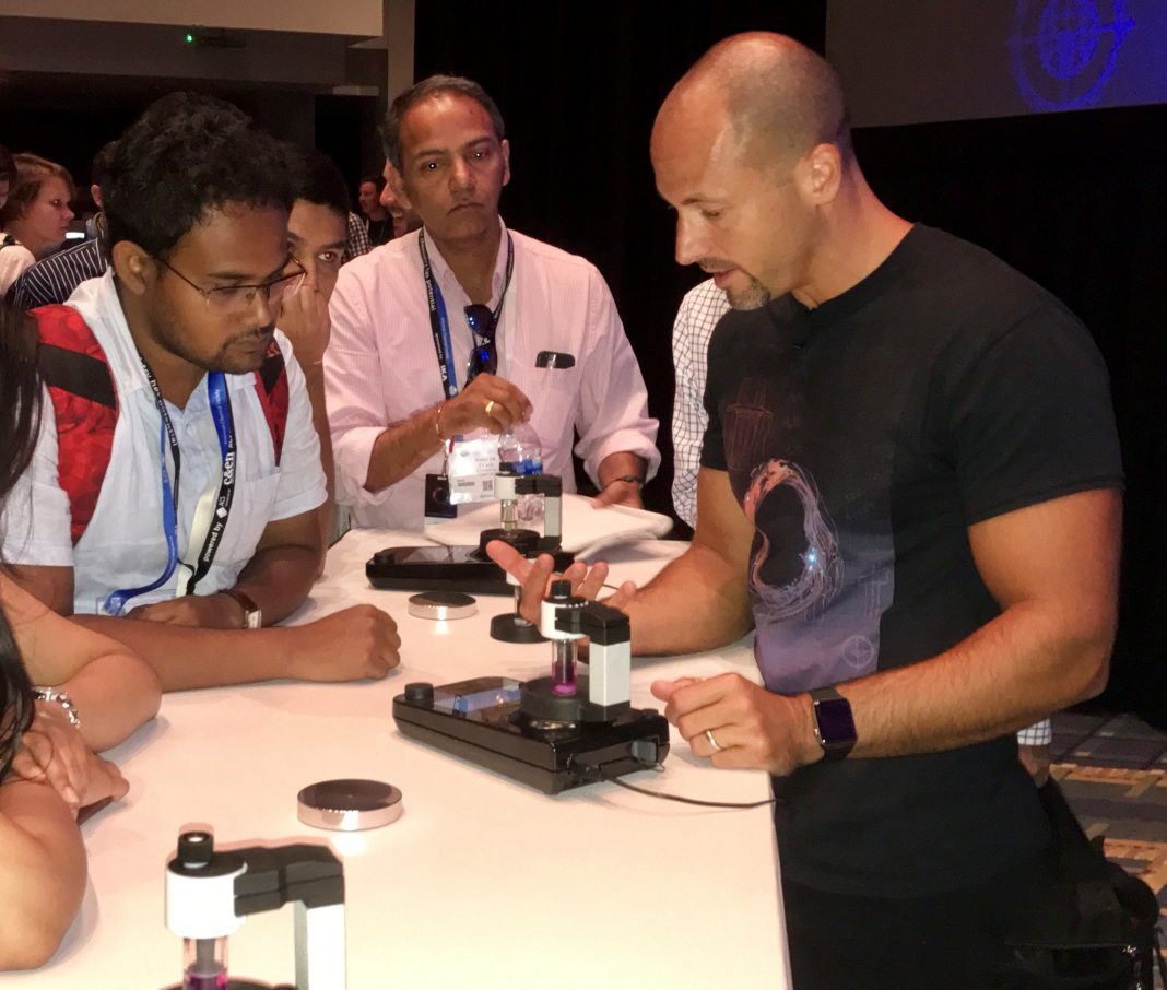 Phil Baran (right) demos the ElectraSyn 2.0 instrument from IKA to eager attendees following his product launch keynote at the ACS National Meeting. [Kevin Davies]