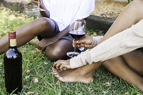 African women on the lawn drinking wine.