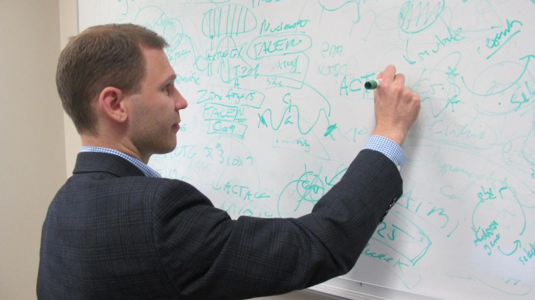 Basil Hubbard writing on white board