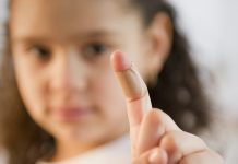 Hispanic girl with bandage on finger
