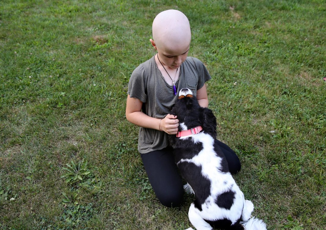 A young girl with cancer, playing with her dog.