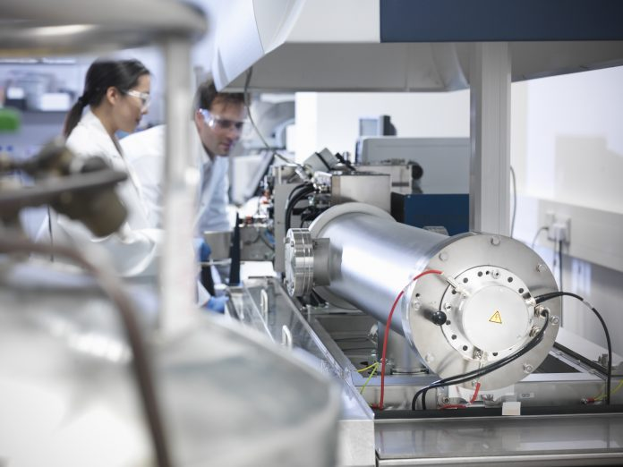 Scientists using a mass spectrometer for molecualr analysis. Proteins are ionised by vaporisation then studied by the relative weight of the diferent ions