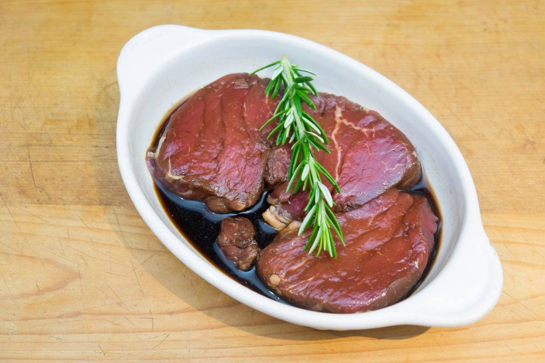 Meat marinating: Beef steak eye fillet in white dish of soy sauce marinade and rosemary herb sprig on wooden background - diagonal composition
