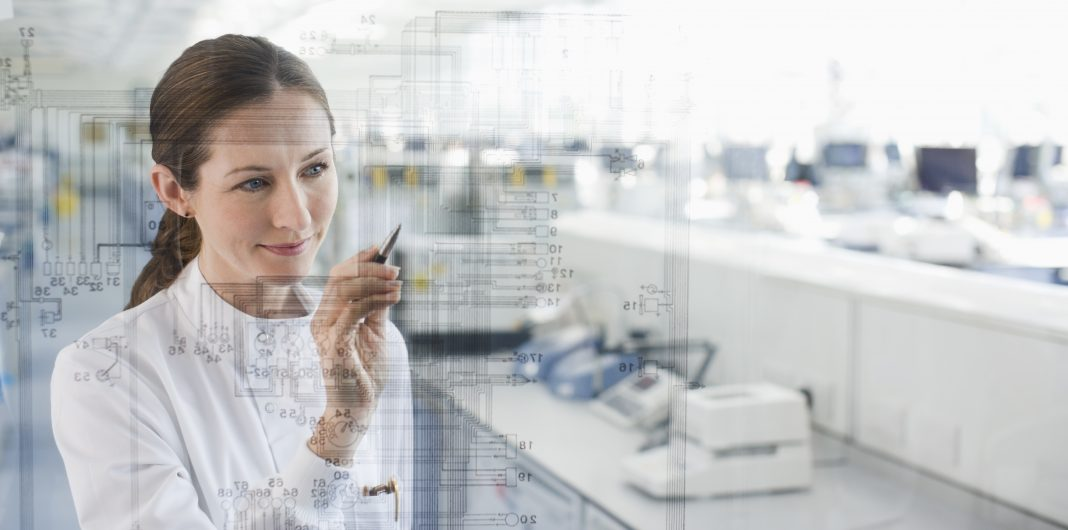 Female scientist using touch screen in lab