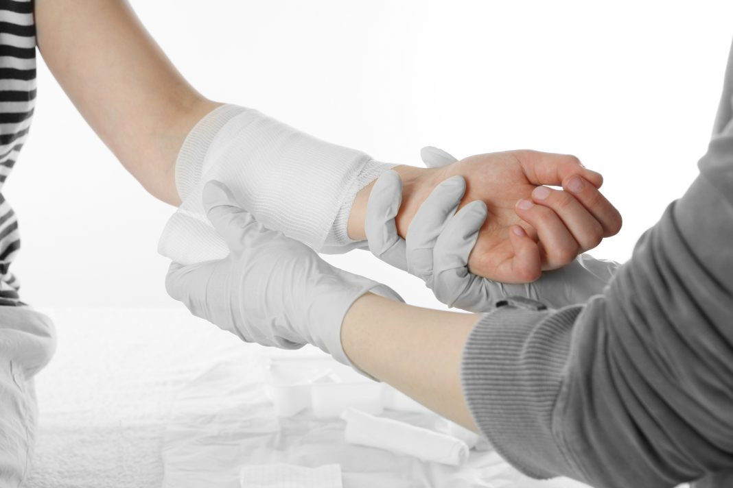 patient getting their arm wrapped with gauze