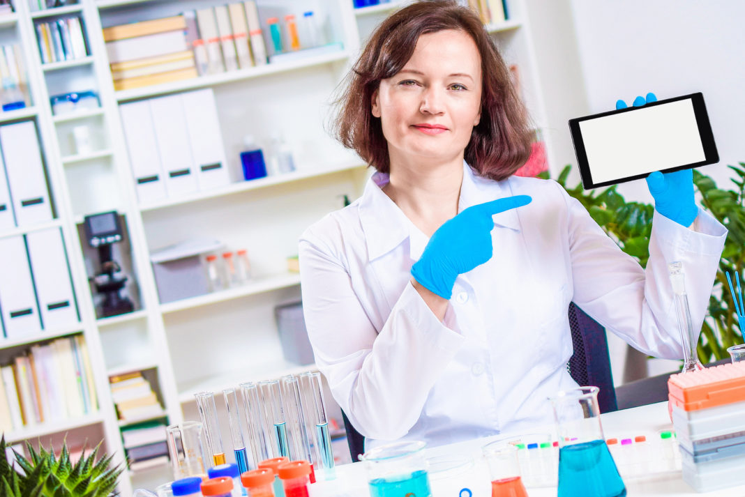female doctor, scientist, or pharmacist holding in hands tablet computer with blank screen. Personalized medicine and smart laboratory. Product presentation. Special offer. Market research.
