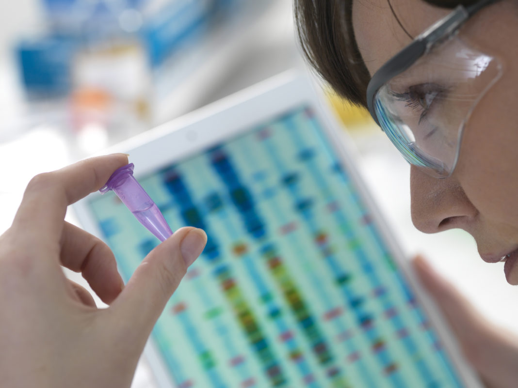 Female scientist examining DNA sample in eppendorf tube with results on digital tablet in laboratory