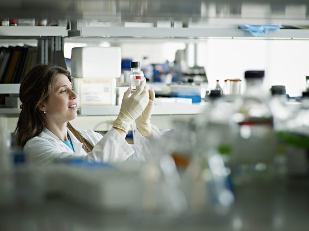 Female scientist examining bottle in research lab