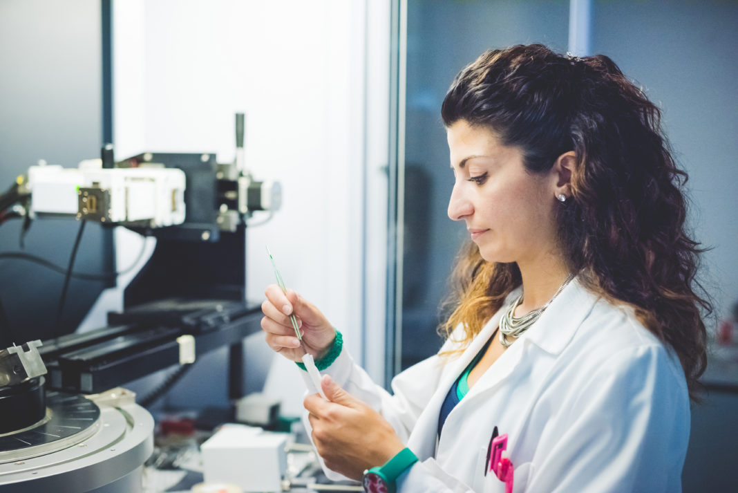 Female scientist preparing thin film sample for measurement with x-ray diffractometer