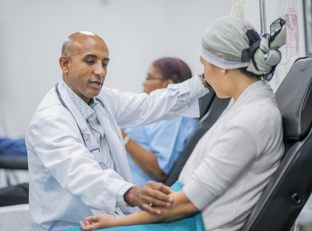 Doctor Giving IV Drip Treatment to Cancer Patient stock photo