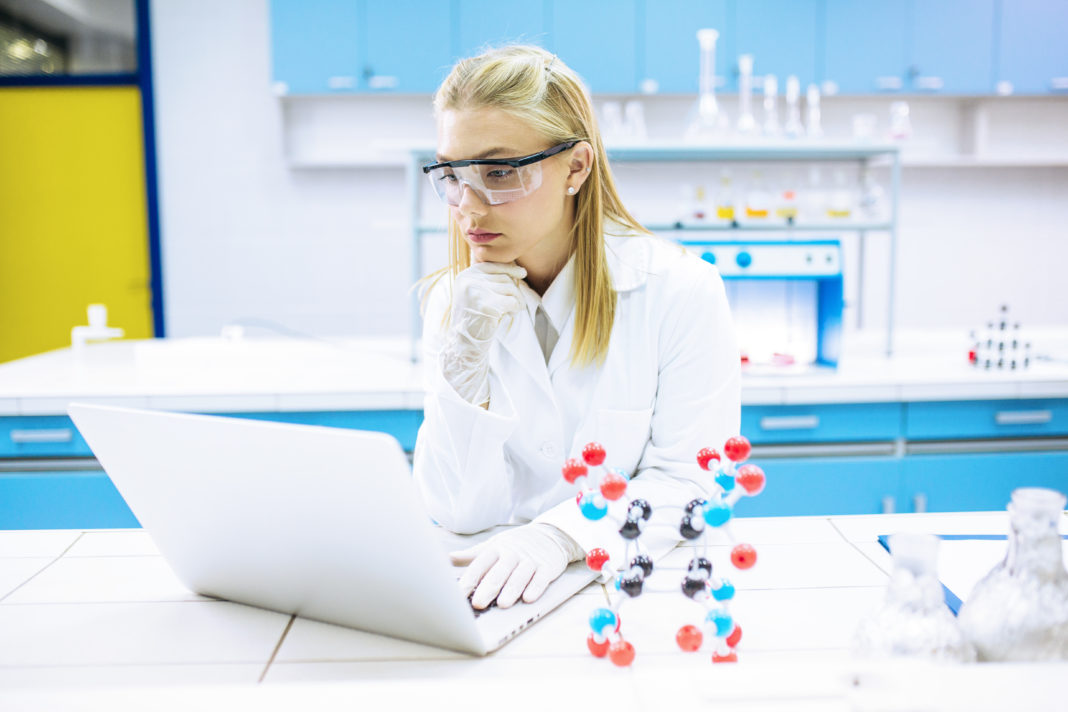 Young Scientist using laptop at laboratory