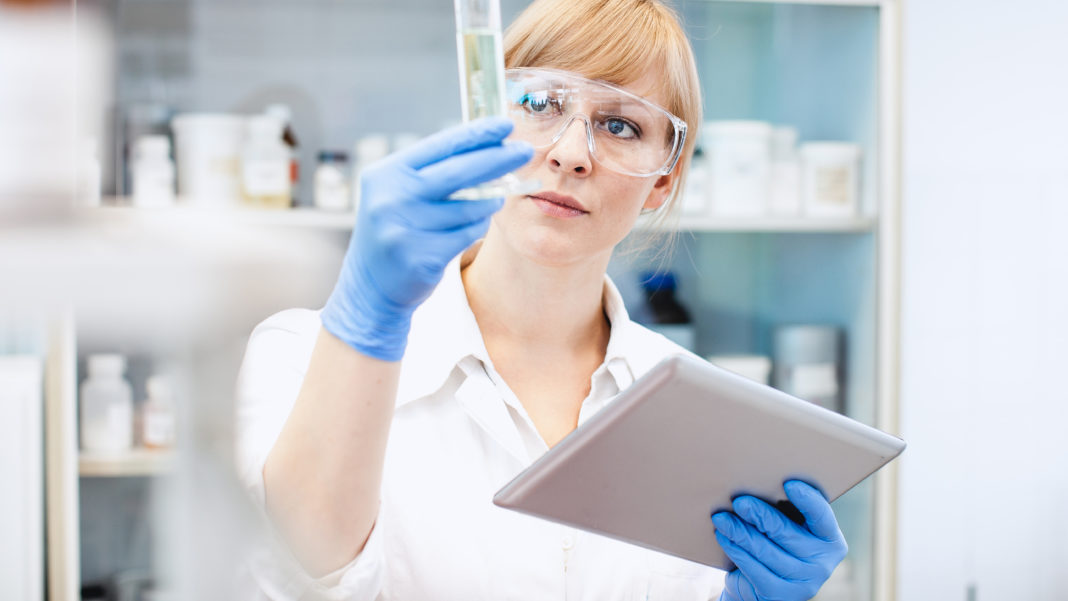 Scientist Looking at Measuring Cylinder,  Holding a Tablet