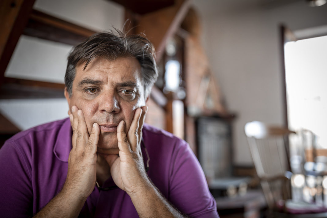 Worried man sitting on bed with hand on forehead in bedroom in serious mood emotion. Major Depressive Disorder called MDD concept. Lonely symptom of men alertness. Physical healthcare and social issue