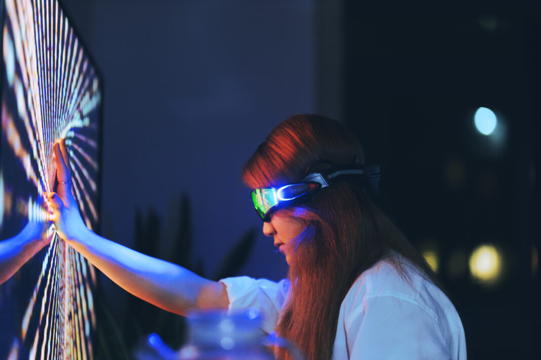 Young woman wearing augmented reality glasses touching screen with hands