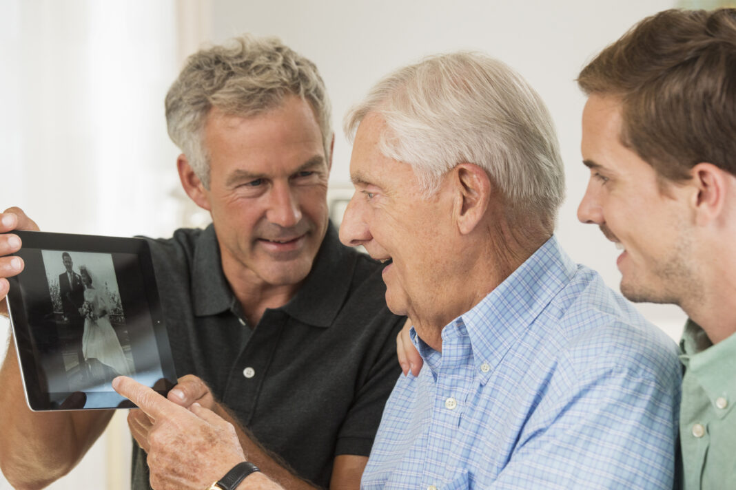 Three generations of Caucasian men using digital tablet