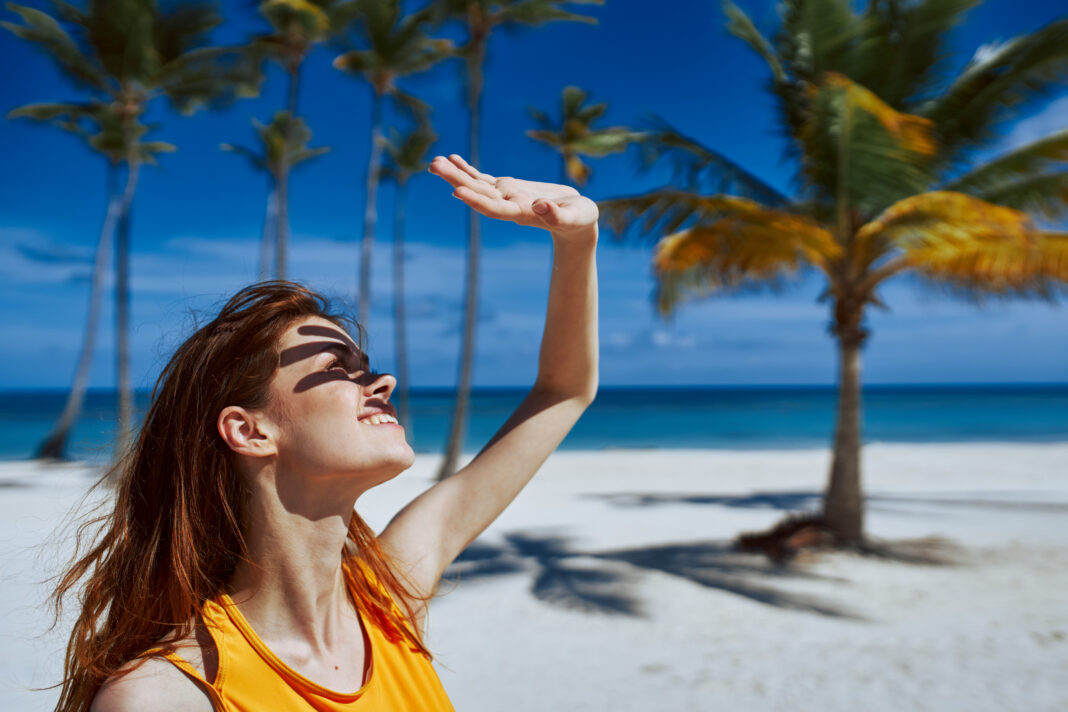 Woman covers her face from the sun with her hand on the beach