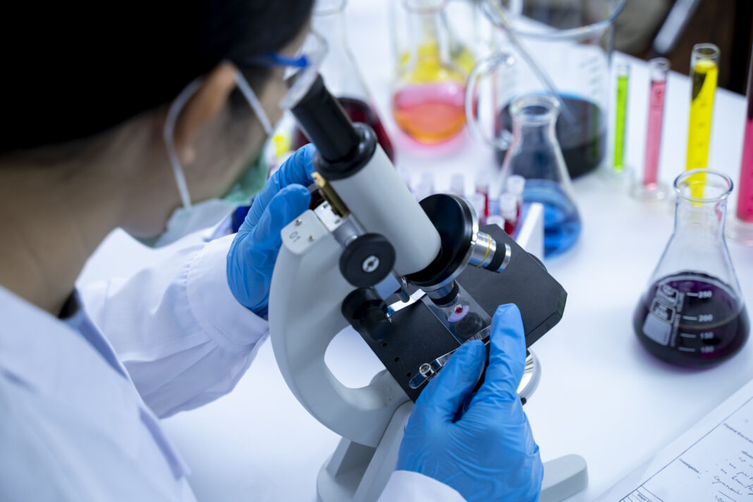 Young Scientist Working With The Microscope