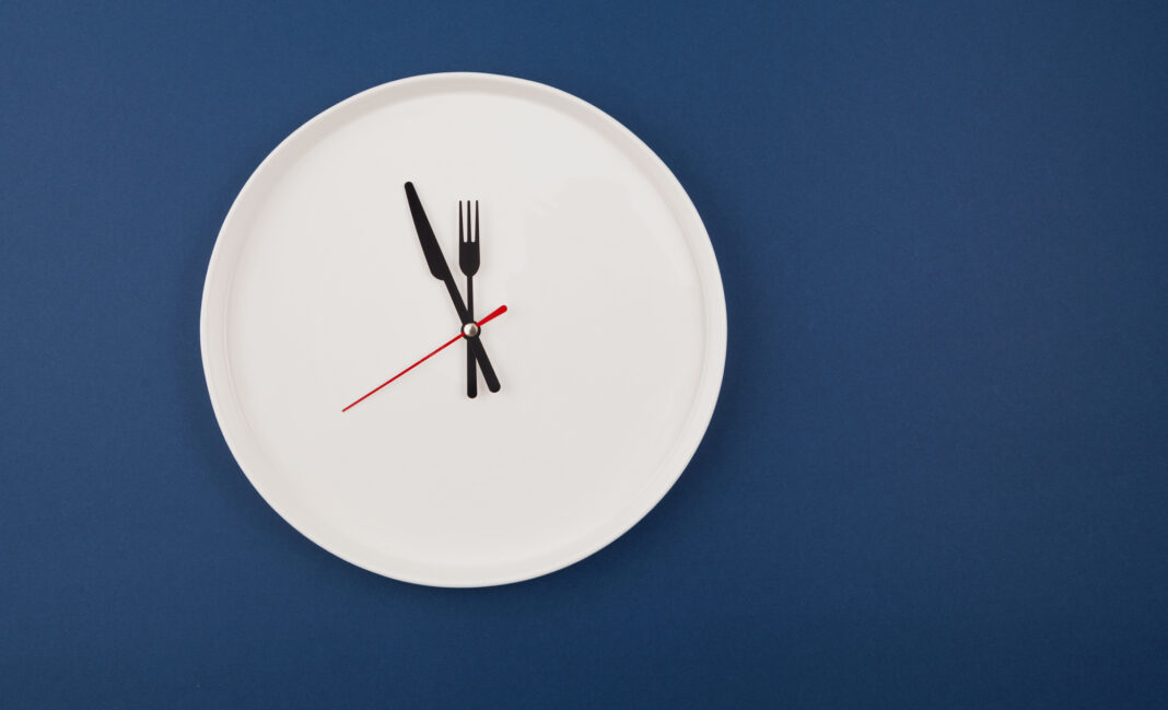 White plate clock on a blue background with copy space. The hands point to 12 o'clock. Interval fasting or autophagy